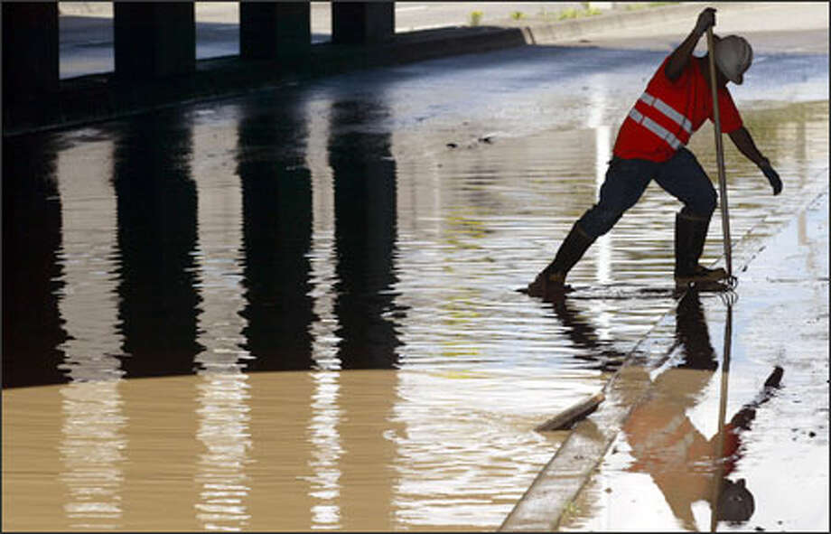 Seattle Public Utilities worker Virgil Anders works to clear a storm drain after a broken water main flooded Broad Street Sunday afternoon. The street was closed while workers shut off the water and cleared the roadway of debris. Gushing water may have undercut the road bed. Photo: Mike Urban/Seattle Post-Intelligencer