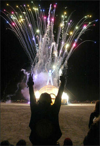 "Fireworks kick off the start of the conflagration that gives the Burning Man festival its name. ""It seems like it's a good wrap for the party,"" Mikey Fisher, 22, of Albuquerque, N.M., said of Saturday's blaze. ""It's just a good release."" Photo: Gilbert W. Arias/Seattle Post-Intelligencer"