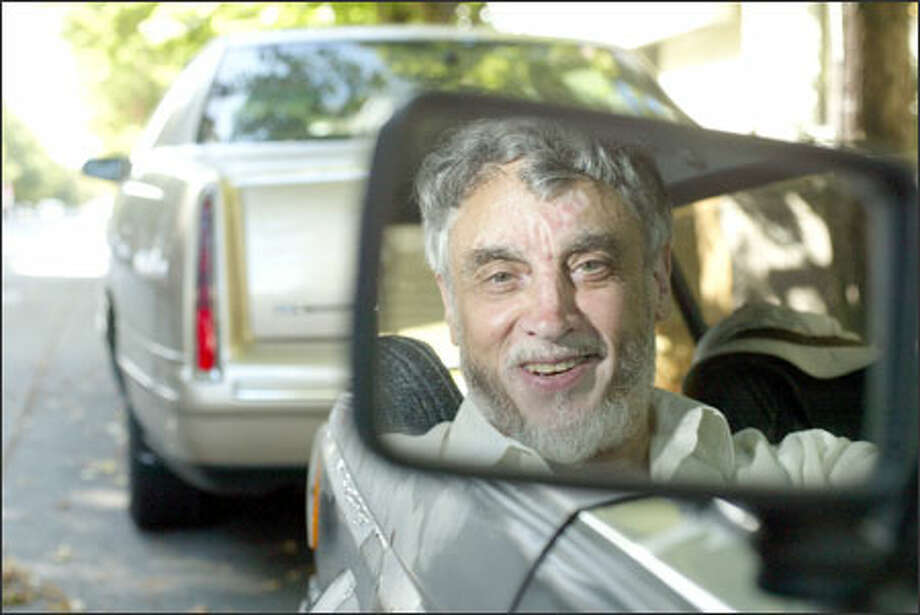"""J.R. """"Jim"""" Joelson, 70, sits in his car yesterday on Northwest 57th Street in Ballard, near where he received three parking tickets soon after the city posted a one-hour limit sign. The sign has been removed, and Joelson will not have to pay fines. """"I'm a low-income senior,"""" he said. """"That's blood money to me."""" Photo: Dan DeLong/Seattle Post-Intelligencer"""