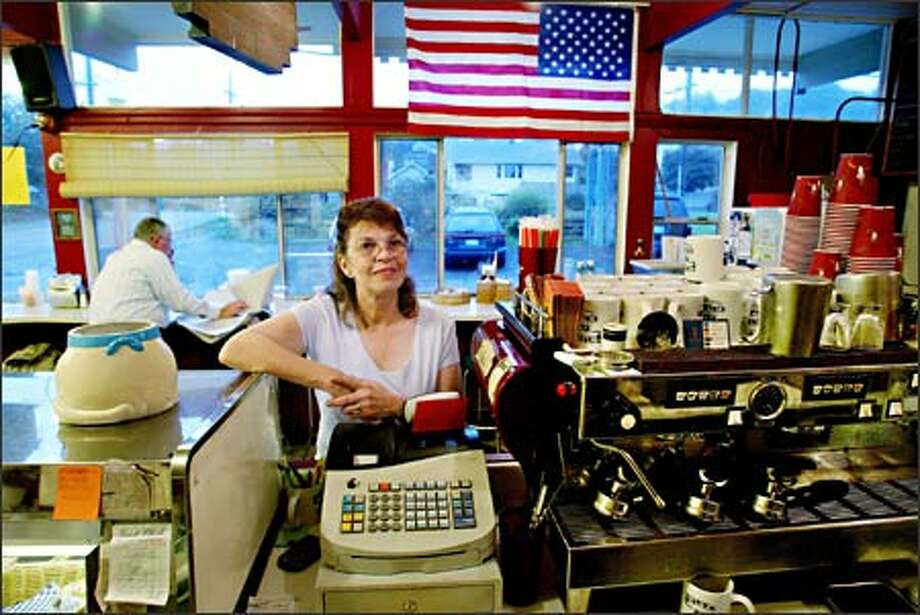 """Penny Ratliff says the flag in her Cat's Eye Cafe in West Seattle """"means 'I love America' not 'I support the president and everything he's doing.' Photo: Paul Joseph Brown/Seattle Post-Intelligencer"""