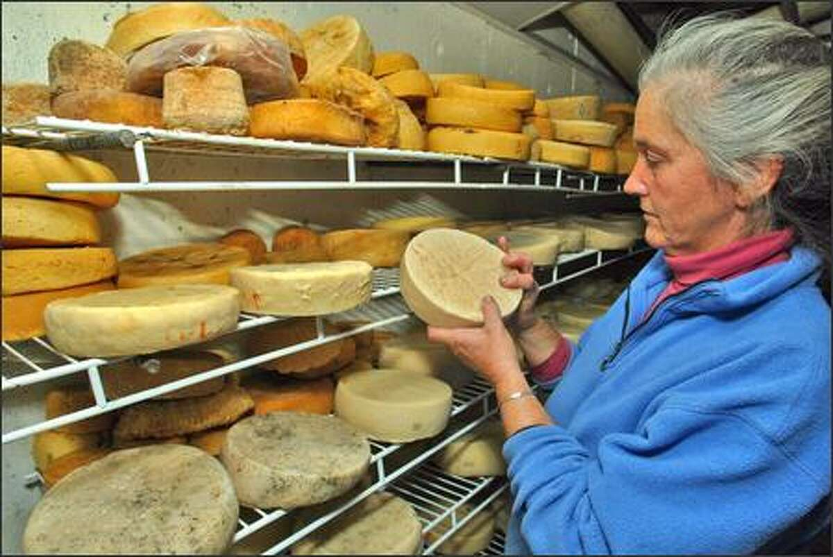 """Lora Lea Misterly checks a wheel of goat cheese in the cheese cellar. Cheeses age at least 60 days. What's hard is not making the cheese, she says, """"but doing it consistently every day and having it look and taste the way you want it."""""""