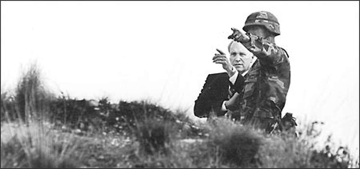 Then-Defense Secretary Dick Cheney observes a live-fire training exercise with Capt. William Lewis at Fort Lewis. The same day in August 1992, before a Seattle audience, Cheney supported the decision not to occupy Iraq but to leave Saddam Hussein in power after the first Gulf War.