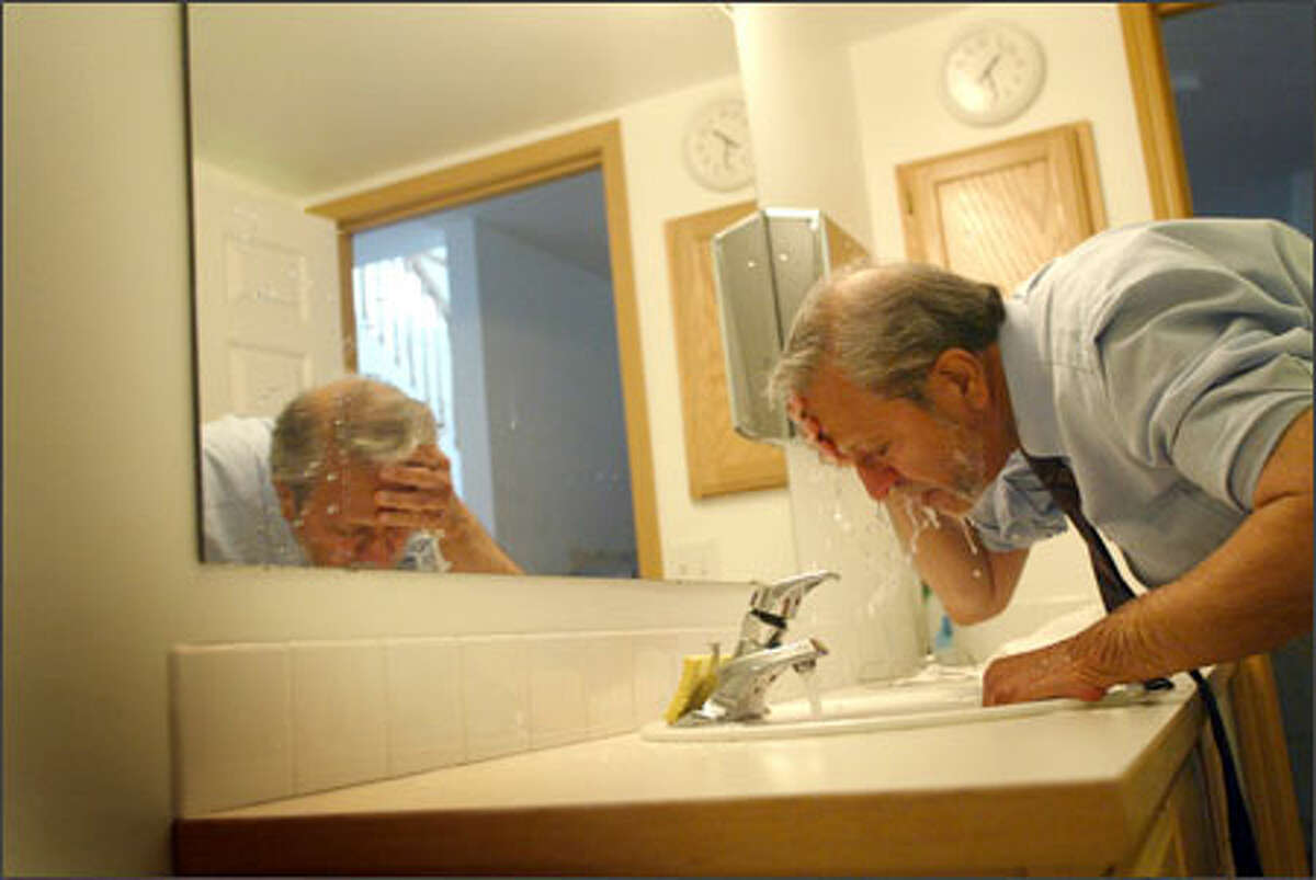Johnny Saiyed makes ablution, the washing of the body, before the Islamic noon prayer Salat-ul-zuhr at his office near the Idriss Mosque in North Seattle. A new poll shows one in four Americans believe several Muslim stereotypes and hold a more negative than positive image of Muslims.