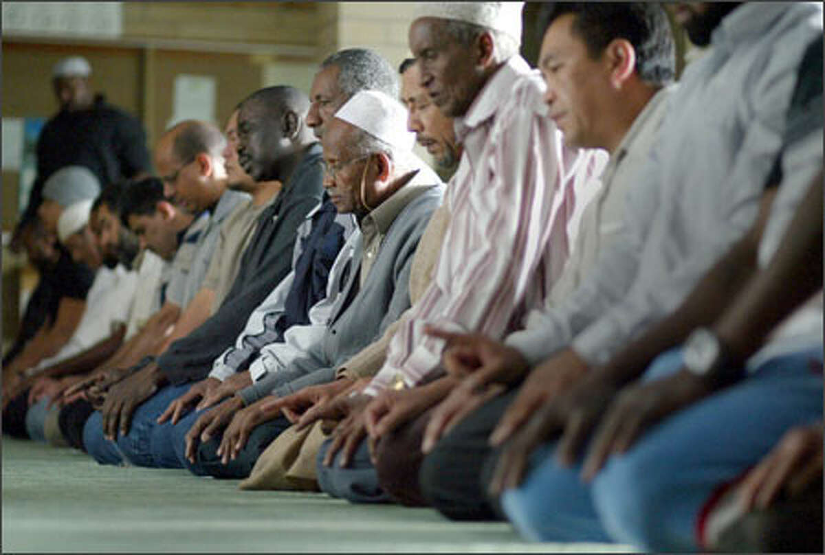 """Men pray during Salat-ul-zuhr at Idriss Mosque. Some in the Muslim community blame the news media for """"disinformation"""" about Islam."""