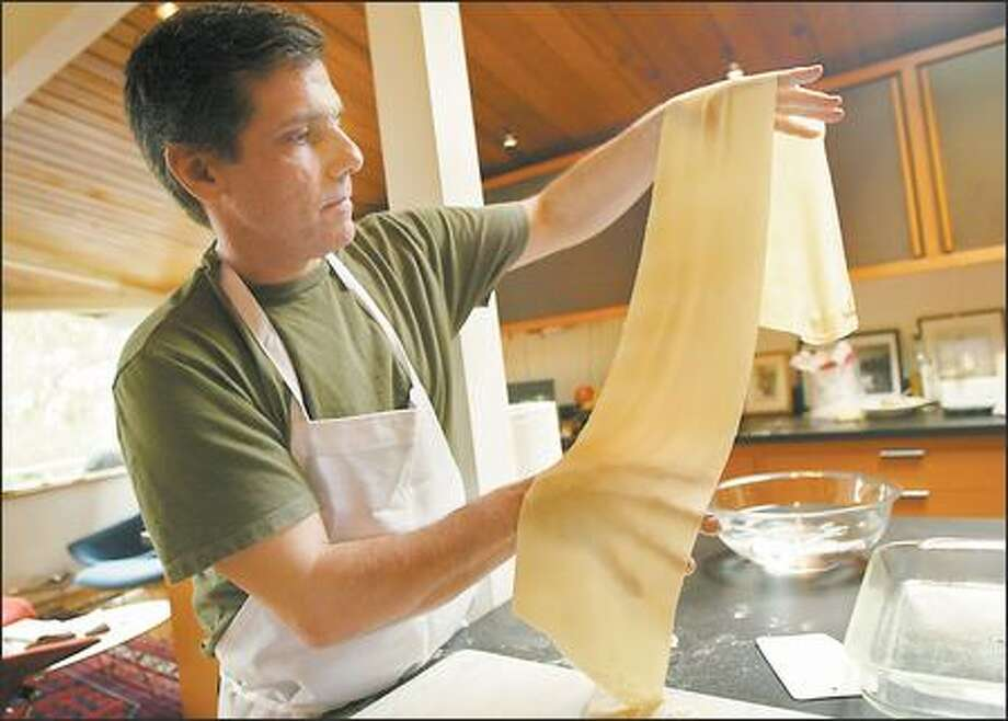 Cafe Lago co-owner Jordi Viladas finishes rolling out a sheet of ultra-thin, yet durable pasta. If your hand is visible through the pasta, the way his hand is, you've done it right. Photo: JOSHUA TRUJILLO/P-I