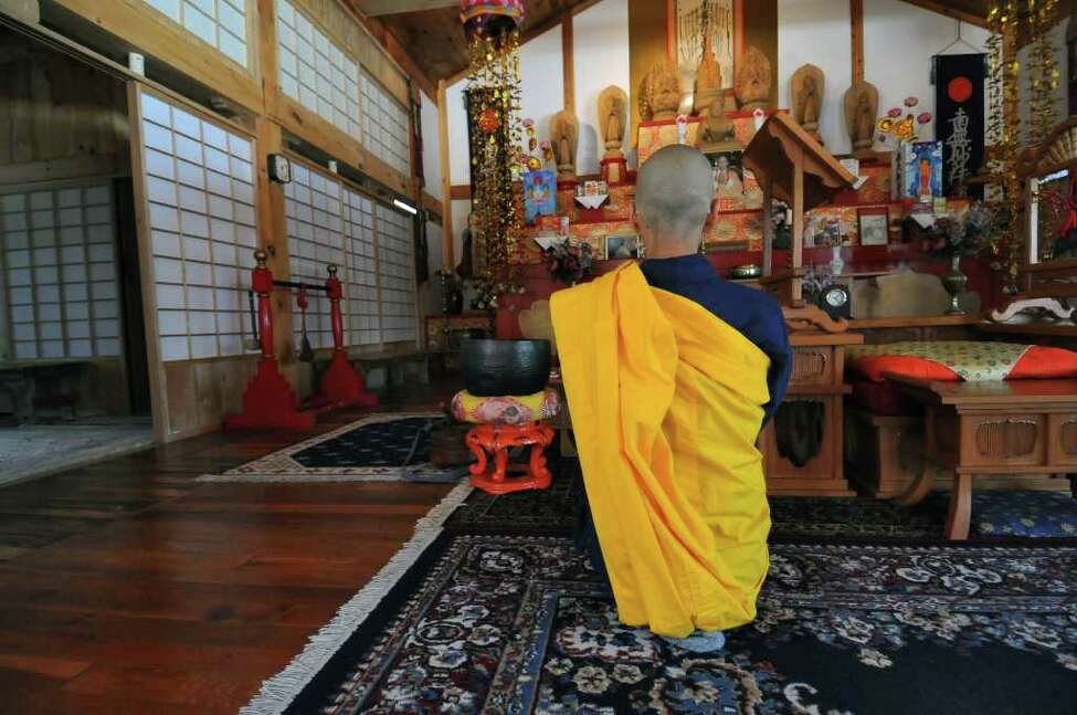 Buddhist nun Jun Yasuda prays for the people of Japan in the temple of the Grafton Peace Pagoda on Tuesday March 15, 2011 in Grafton, NY. She grew up in Tokyo. ( Philip Kamrass / Times Union )