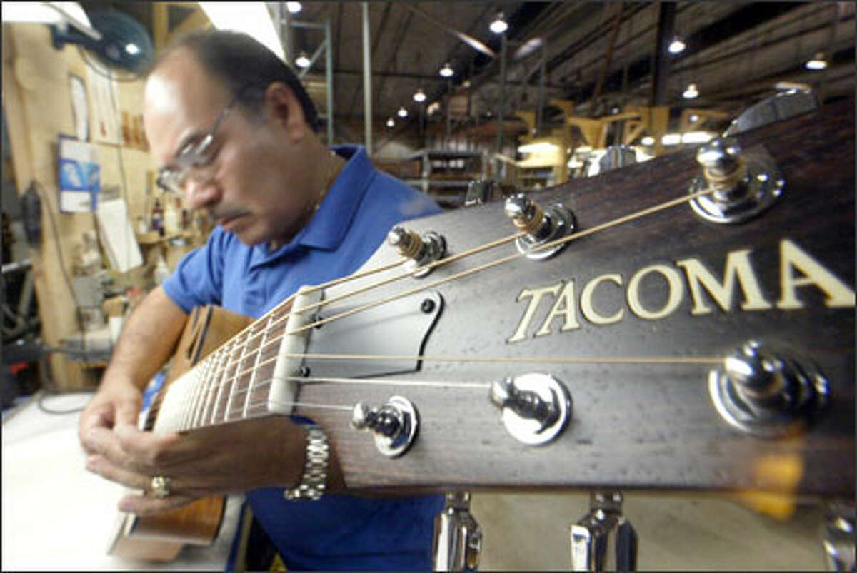 Juan Herrejon tests a new instrument during the final assembly at Tacoma Guitar Co., which makes 7,000 to 10,000 instruments annually.