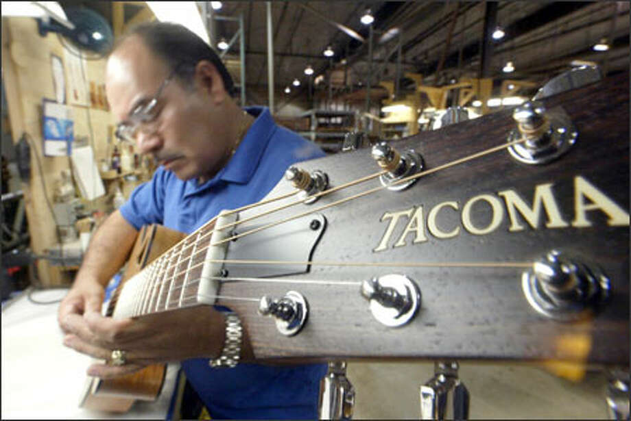 Juan Herrejon tests a new instrument during the final assembly at Tacoma Guitar Co., which makes 7,000 to 10,000 instruments annually. Photo: Phil H. Webber/Seattle Post-Intelligencer