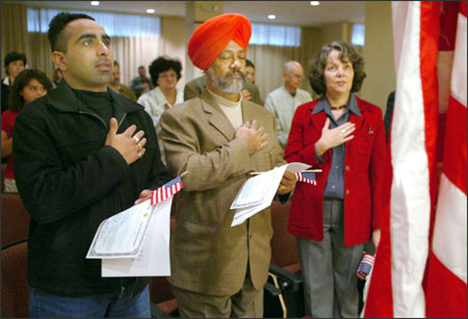 From left, Harpreet Singh, Lakhwinder Singh Bhachu and Beatriz Aramburu recite the Pledge of Allegiance during their oath of citizenship at the Department of Homeland Security yesterday in Tukwila. They registered to vote right after the ceremony in the federal office. Photo: Joshua Trujillo/Seattle Post-Intelligencer
