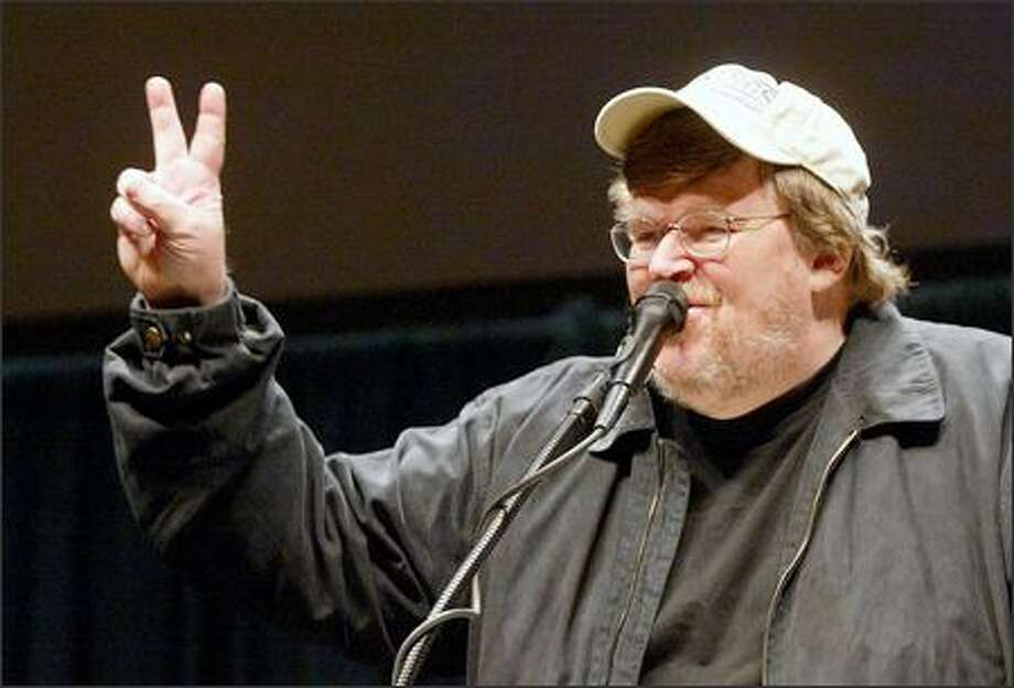 """Two more weeks,"" filmmaker Michael Moore tells a near full house at KeyArena last night. He drew a boisterous response -- and protesters. Photo: Mike Urban/Seattle Post-Intelligencer"