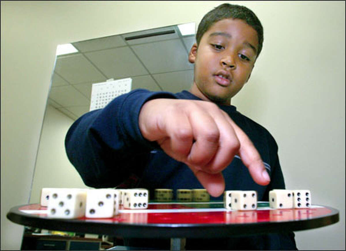 Kumar reaches for a die on a rotating turntable covered with dice. He picks them up in different order. The exercise is designed to assist Kumar to track something while it is in motion.