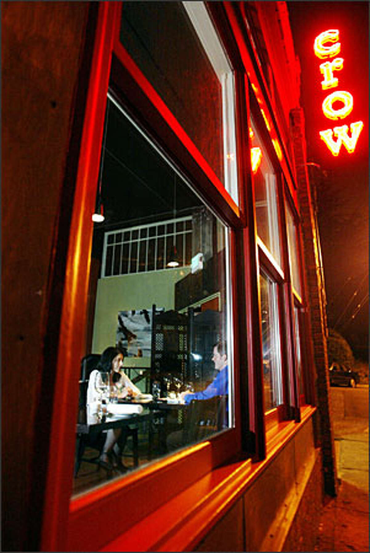 Customers enjoy dinner at Crow Restaurant & Bar on Lower Queen Anne. The converted warehouse space retains the loose, open feel of its past life.