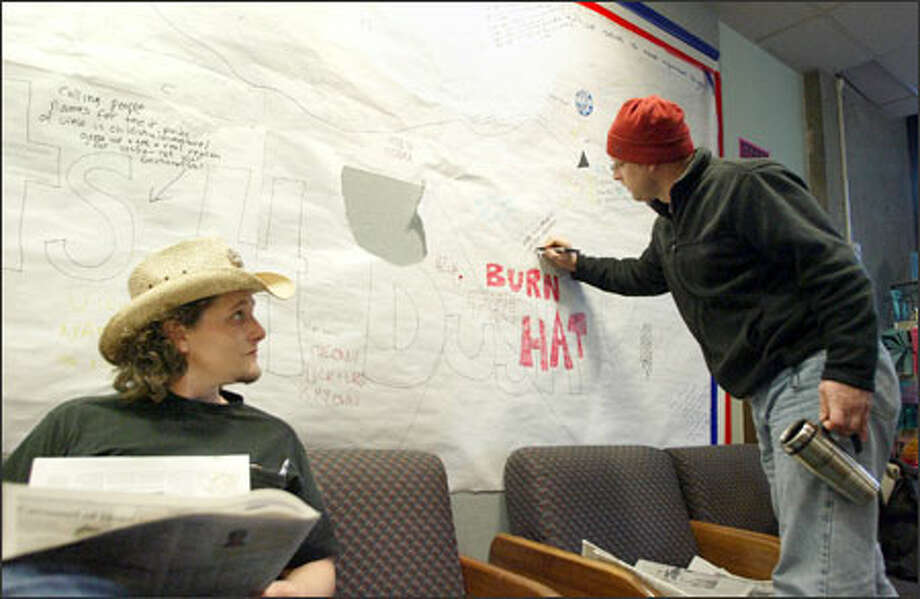 John Sandifer, 33, a libertarian, left, watches Joel Cochran, 38, add his political opinion to a paper wall at North Seattle Community College. Photo: Meryl Schenker/Seattle Post-Intelligencer