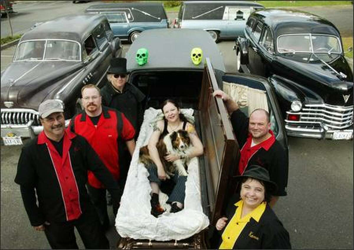 Members of the Rain City Hearse Club pose with their cars.