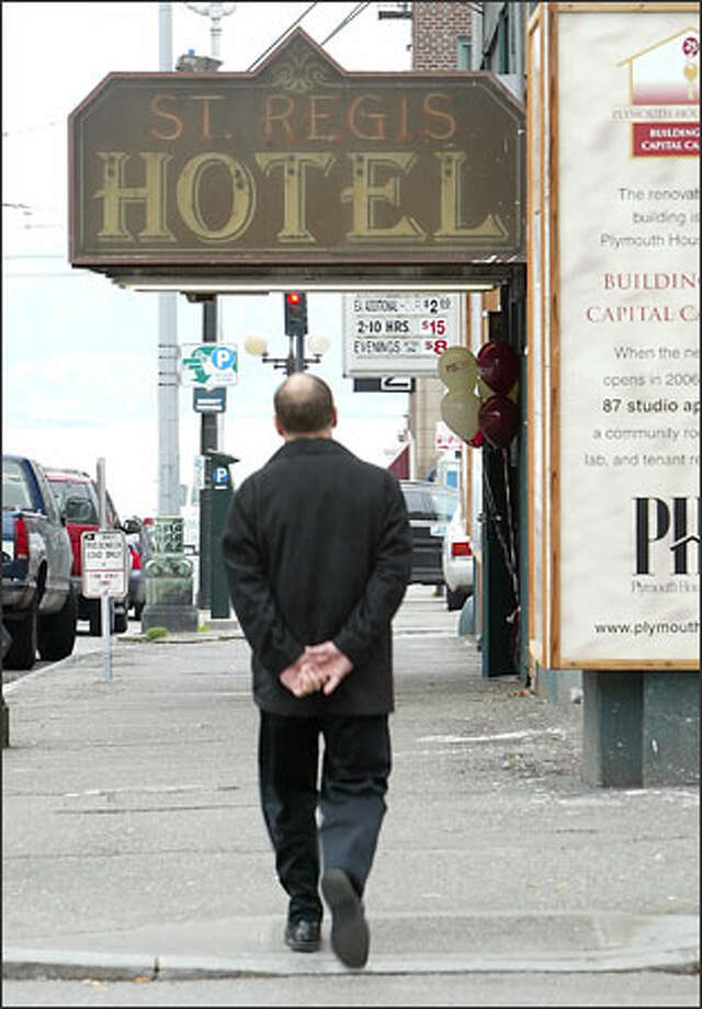 A pedestrian strolls past the old St. Regis Hotel at Second and Stewart in downtown Seattle. Photo: Gilbert W. Arias/Seattle Post-Intelligencer