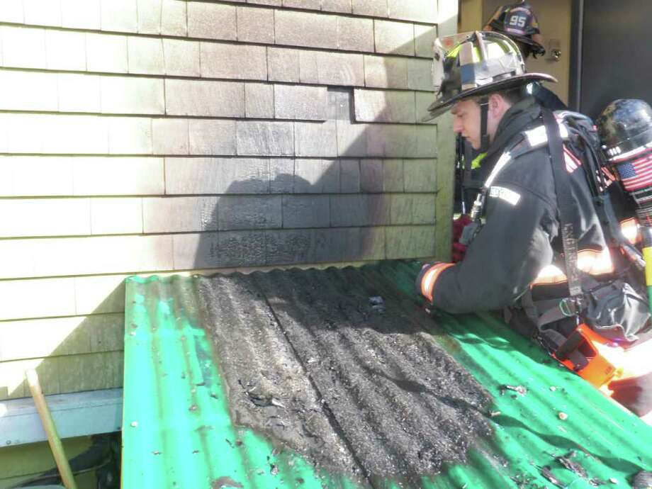 A Westport firefighter inspects the damage caused by a fire Wednesday afternoon at the Dressing Room, a restaurant that was co-owned by screen legend Paul Newman. The Dressing Room is located at 27 Powers Court. Photo: Contributed Photo / Westport News