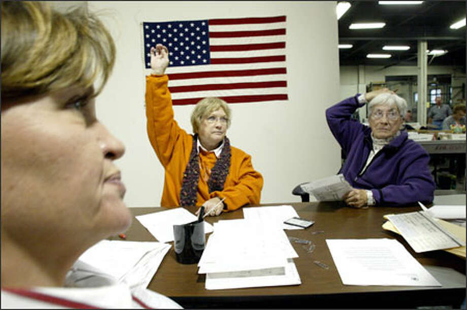 Under the watchful eye of GOP observer Jamie Daniels, left, King County election workers Laura Warren, center, and Pat Eide get a supervisor's attention for a question while processing provisional ballots yesterday. Photo: Dan DeLong/Seattle Post-Intelligencer