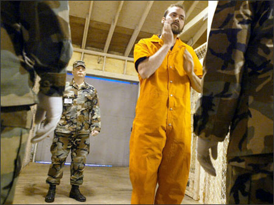 During a training exercise at Fort Lewis, Staff Sgt. Jonathan Cline role-plays a detainee going through a procedural check with the guards. Photo: Meryl Schenker/Seattle Post-Intelligencer