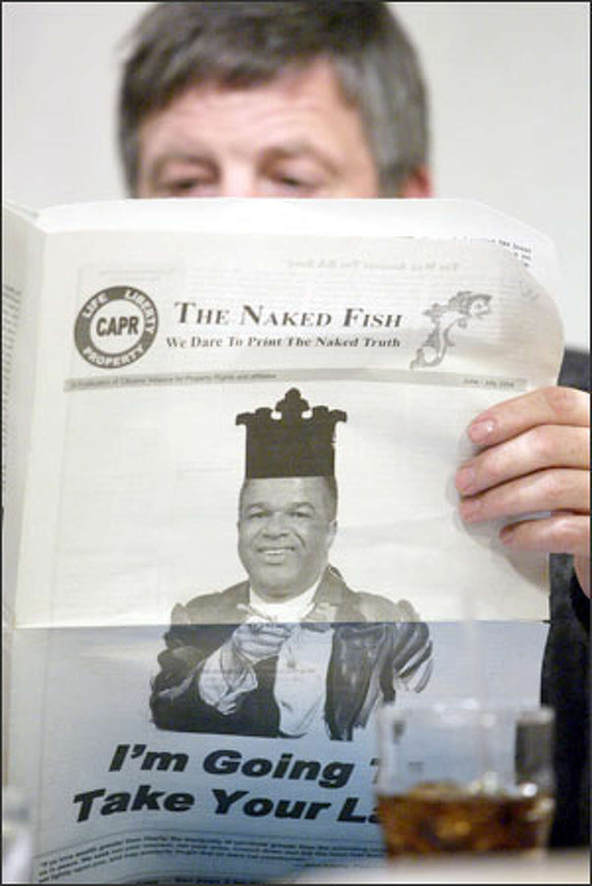 Roy Ruffino of Lacey reads the Citizens Alliance for Property Rights newsletter featuring a reworked photo depicting King County Executive Ron Sims as