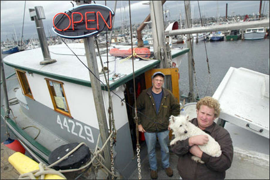 Mark, left, and Conan Johansen sell fish from their boat, the F/V Cora J at Fishermen's Terminal. The brothers hold their dog, Dolly, in higher regard than the fish they catch. Photo: Karen Ducey/Seattle Post-Intelligencer