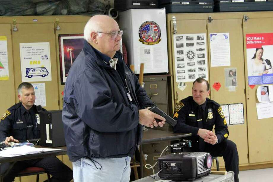 Jack Codeanne, a member of the Milford Citizens Police Academy class, waits for a cue to enter a simulated crime scene. Det. Frank Gall, left, operates the computer program that projects interactive scenarios on a screen while Sgt. Vaughan Dumas coaches students. Photo: Frank Juliano / Connecticut Post