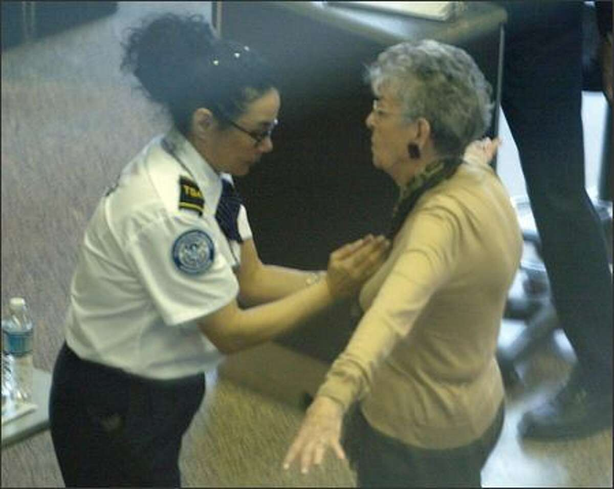 A Transportation Security Administration employee pats down a traveler as she passes through the north checkpoint at Sea-Tac Airport.