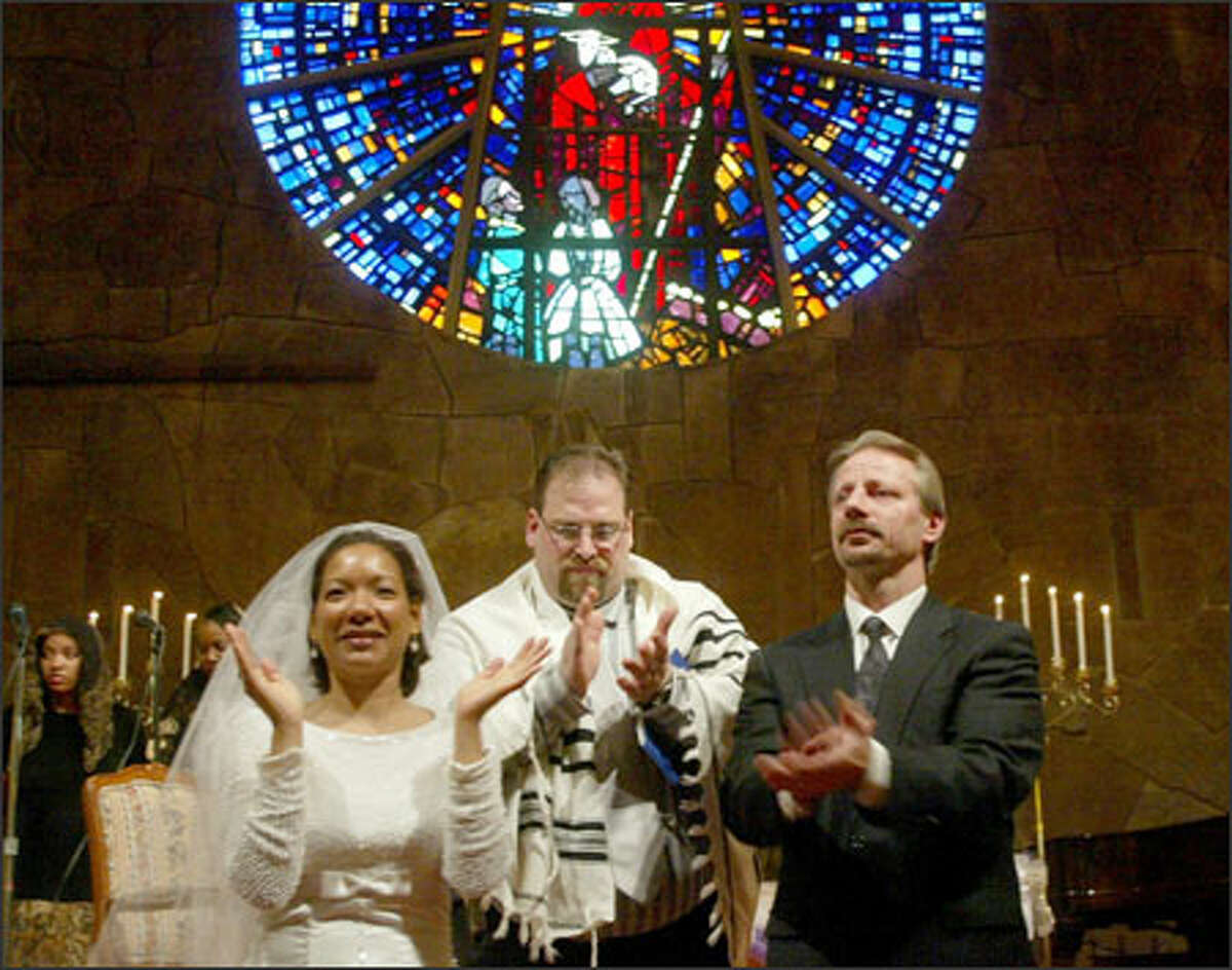 Pastor James Noriega, center, presents bride Susana Urbaez and groom Brian Ostertag to the congregation during their wedding in Seattle yesterday.