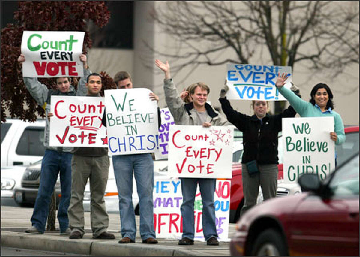 Supporters of Christine Gregoire rally outside the campaign headquarters of Republican Dino Rossi shortly before Rossi had a news conference in Bellevue.