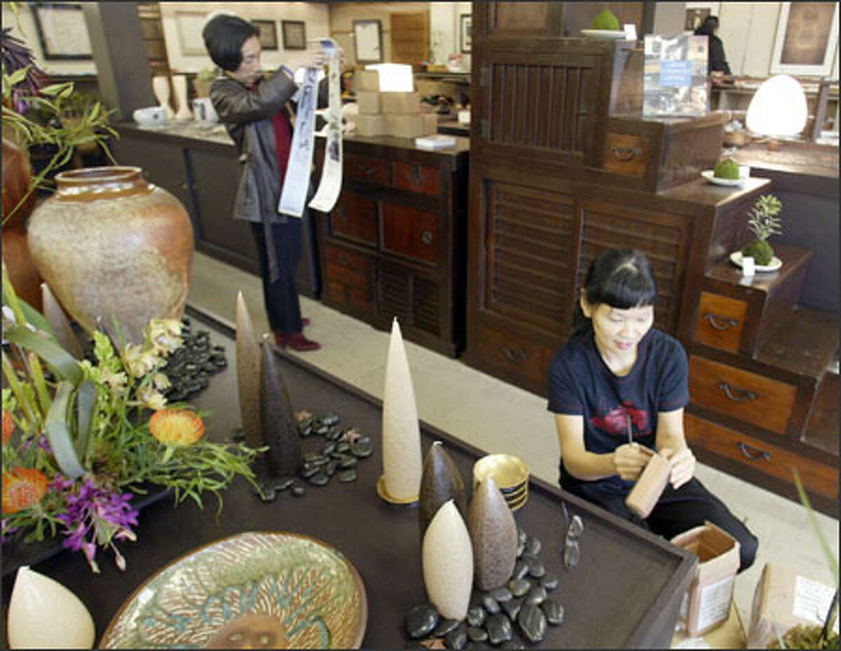 Binko Chiong-Bisbee, right, co-owner of Kobo at Higo, arranges a display at the new shop in the International District as Sachi Crowden shops.