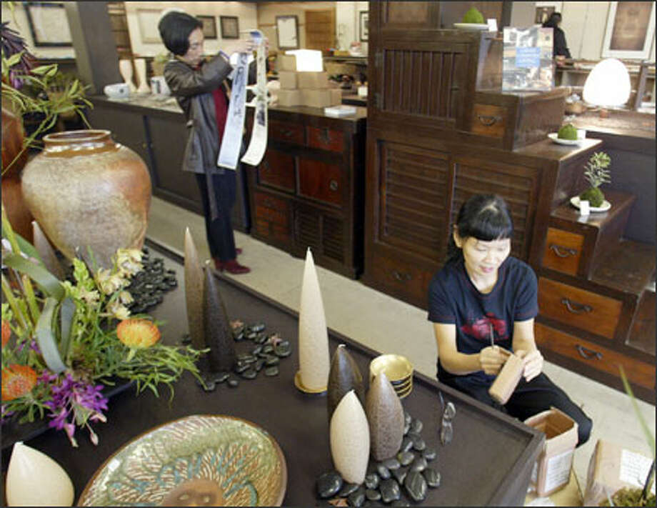 Binko Chiong-Bisbee, right, co-owner of Kobo at Higo, arranges a display at the new shop in the International District as Sachi Crowden shops. Photo: Phil H. Webber/Seattle Post-Intelligencer