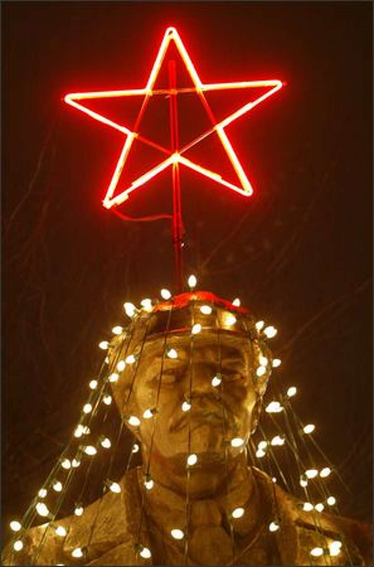 Folks in Fremont gathered last night for the lighting ceremony at the Lenin statue. Strings of light created a Christmas tree around the statue, complete with a shining red star on his hat.