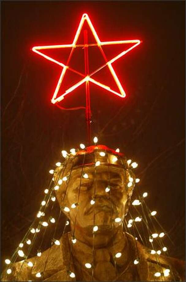 Folks in Fremont gathered last night for the lighting ceremony at the Lenin statue. Strings of light created a Christmas tree around the statue, complete with a shining red star on his hat. Photo: Dan DeLong/Seattle Post-Intelligencer