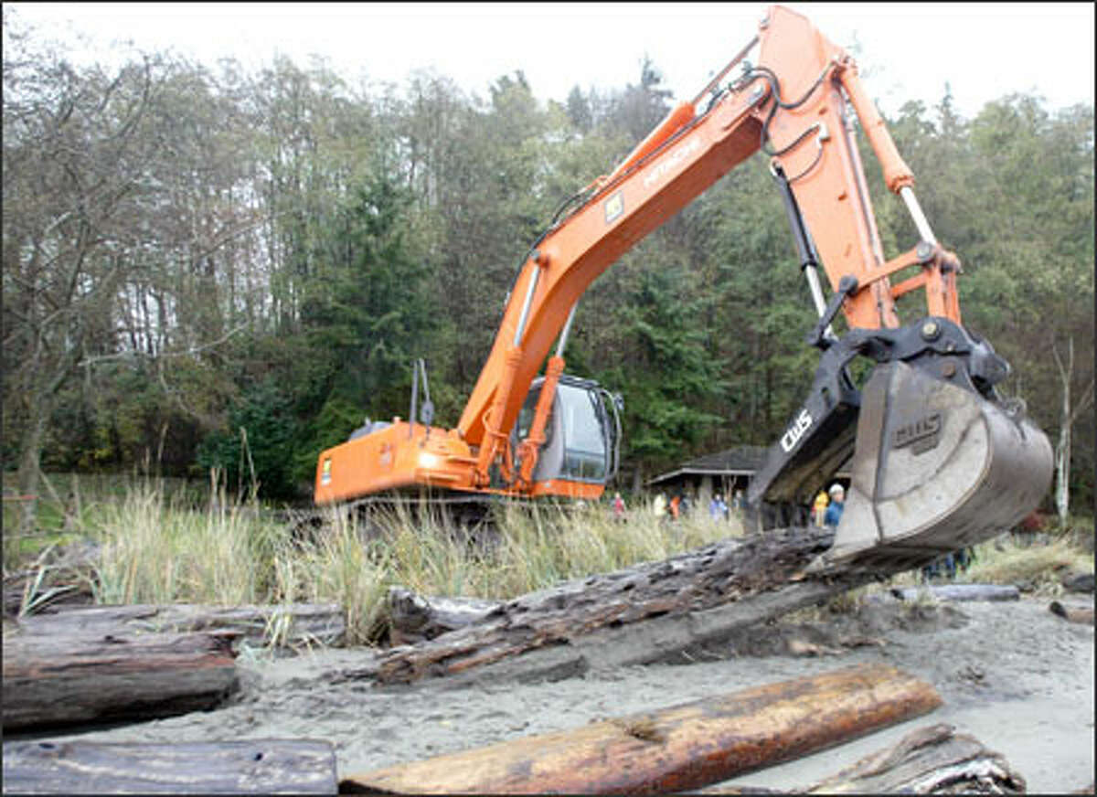 Tom Myler uses an excavator to remove driftwood along Seahurst Park's south sea wall as work begins on the park's shoreline restoration project. When completed, the section of the beach will be part of a two-thirds of a mile stretch of natural, unwalled beach habitat on Puget Sound.