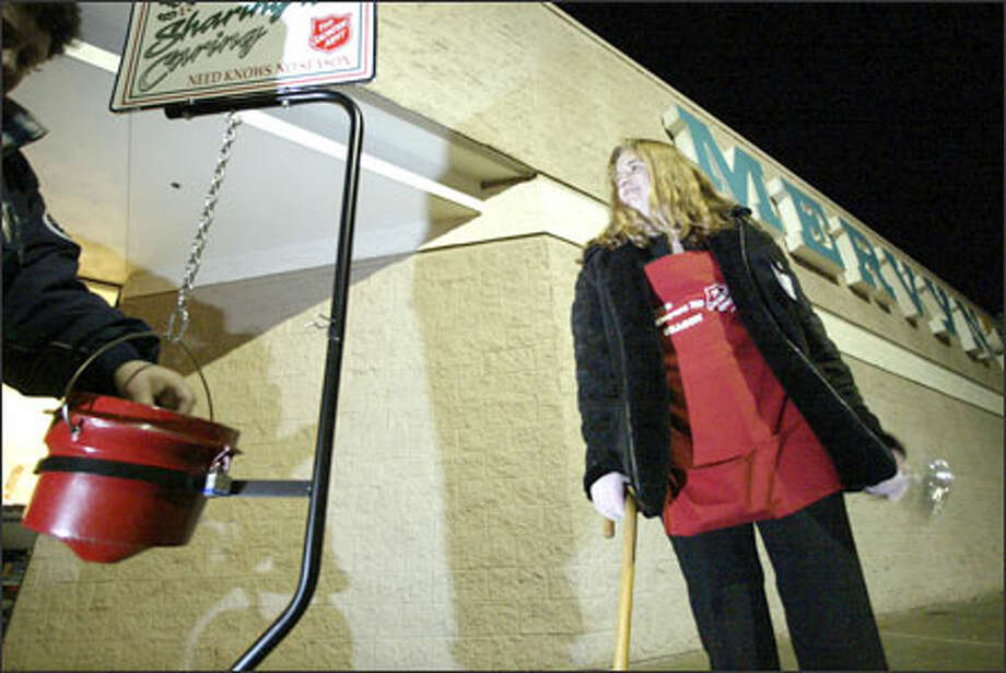 Salvation Army bell ringer Christina Wade watches someone put a donation in her bucket outside Mervyn's department store at Silverdale Mall on Kitsap Peninsula. Photo: Jim Bryant/Seattle Post-Intelligencer