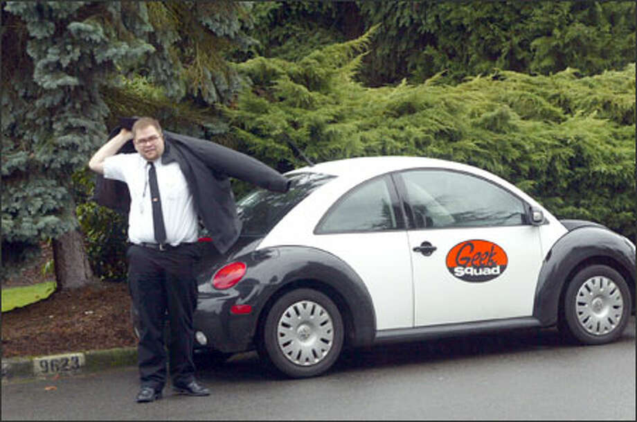 Wearing the trademark black and white get-up of the Geek Squad, Fred Deichler prepares to enter the home of a customer in Redmond this week. Photo: Phil H. Webber/Seattle Post-Intelligencer / SEATTLE POST-INTELLIGENCER