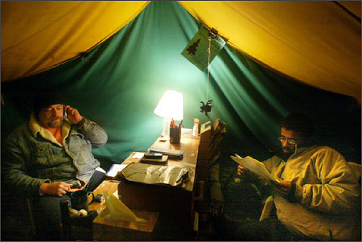 At 6 a.m., Kevin Pellow, left, prepares to take over a work shift from Vijay Lih at the office tent at Tent City 4. The office is staffed at all times.