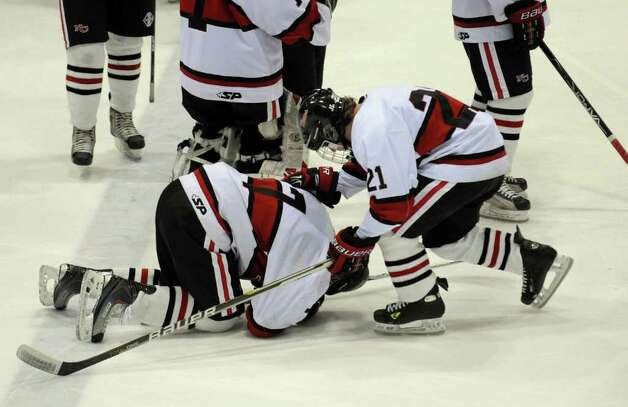 New Canaan's #21 Tom Picard, right, bends over to comfort teammate #7 Brian Tohir after the team lost to St. Joseph, during CIAC Class I semifinal boys hockey action against St. Joe's at Yale's Ingalis Rink in New Haven, Conn. on Wednesday March 16, 2011. Photo: Christian Abraham / Connecticut Post