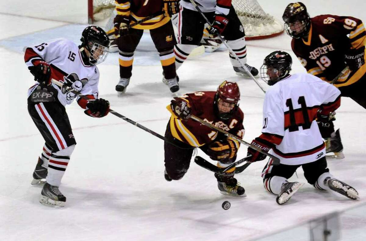 St. Joseph's #10 Conor Crouse, center, tries to get to the puck between New Canaan players #15 Dylan Hart, left, and #19 Reed Harper, right, during CIAC Class I semifinal boys hockey action at Yale's Ingalis Rink in New Haven, Conn. on Wednesday March 16, 2011.