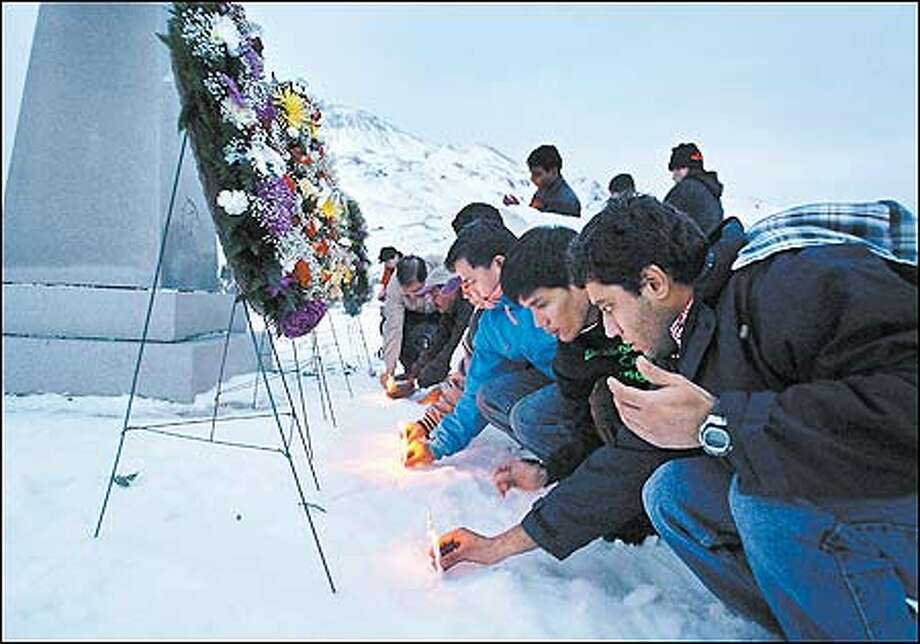 Surviving crew members place candles in the snow at the Fisherman's Memorial Park yesterday in Dutch Harbor, Alaska. Photo: Joshua Trujillo/Seattle Post-Intelligencer