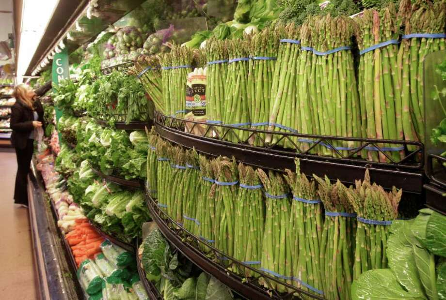 In this March 1, 2011 photo, a customer looks at fresh vegetables at a Kroger Co. supermarket in Cincinnati. Wholesale prices jumped last month by the most in nearly two years due to higher energy costs and the steepest rise in food prices in 36 years. (AP Photo/Al Behrman) Photo: Al Behrman