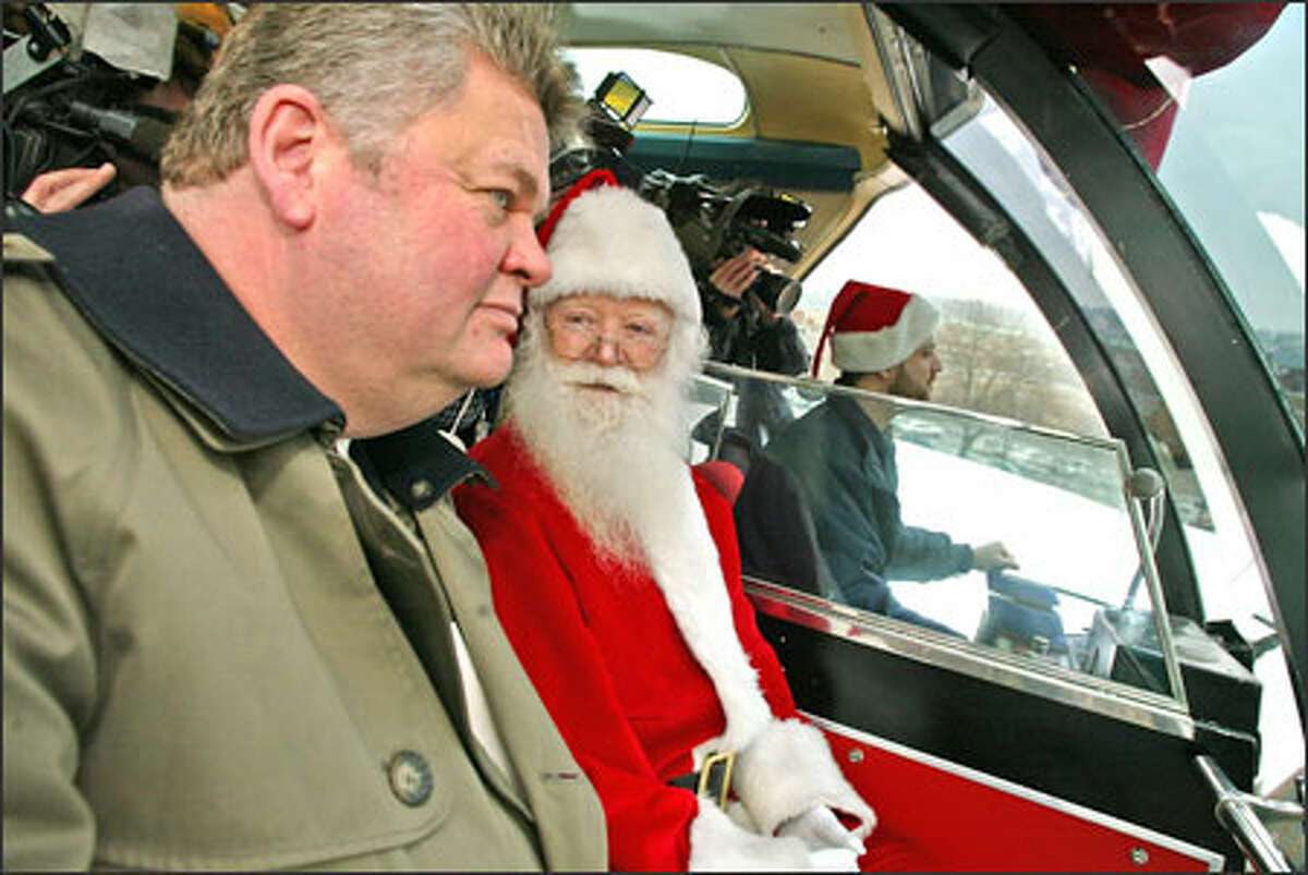 Seattle Mayor Greg Nickels chats with Santa while riding the old Monorail, which reopened after several months of repair work following a fire.