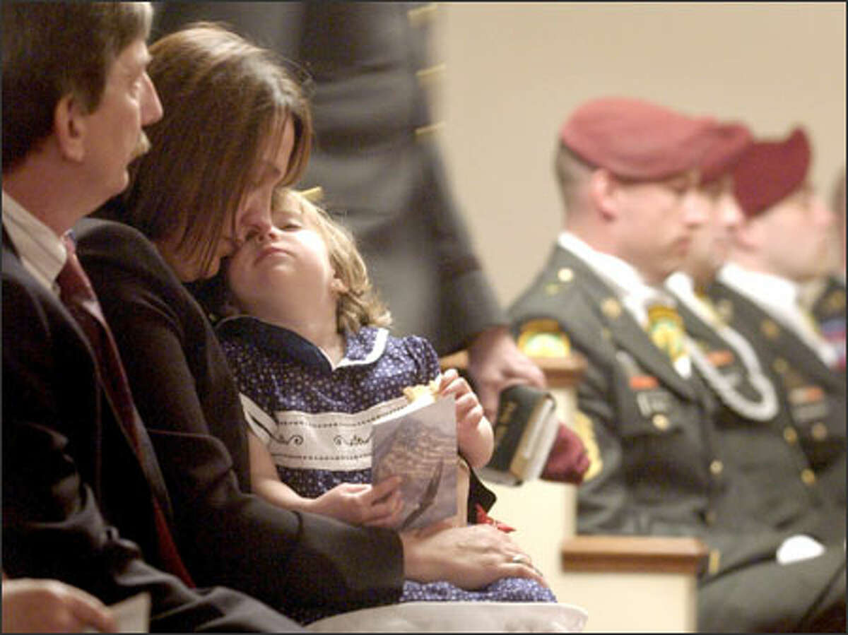 Corey Shanaberger holds her 3-year-old daughter, Grace, during the funeral for her husband, Army Staff Sgt. Wentz