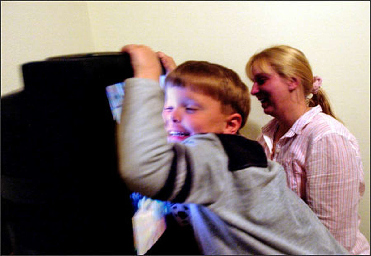Dakota Givens hugs the television in his room as he asks his mother, Melissa Givens, to rewind a videotape that his father, Army Pfc. Jesse Givens, made for him. Givens, 34, of Fountain, Colo., was killed in Iraq in May 2003 and left behind a wife and two sons, including a baby he never got to see.