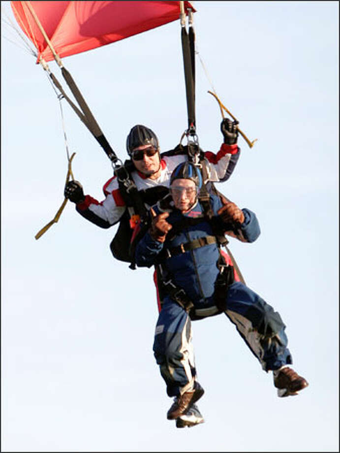 Milburn Hart, 96, and Vladimir Ursachii, rear, come in for a landing during a tandem skydive at Harvey Field in Snohomish. Hart had scheduled to jump on Friday, his birthday, but had to wait a day because of bad weather. Photo: Ron Wurzer/Seattle Post-Intelligencer