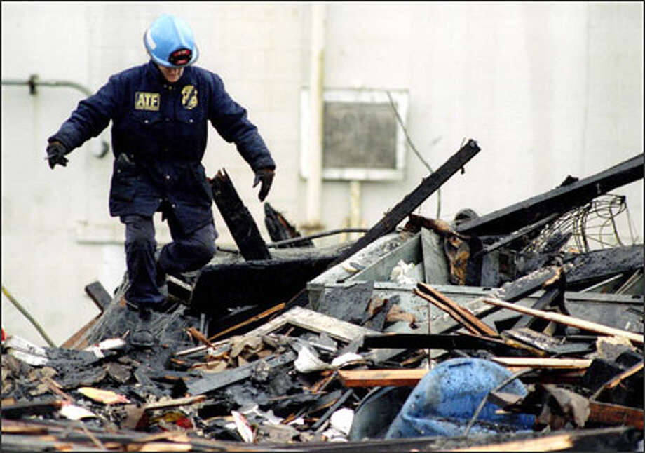 An investigator searches the Mary Pang's Food Products plant after the 1995 fire. Martin Pang, son of the building's owner, was convicted of arson. Photo: P-I File/1995