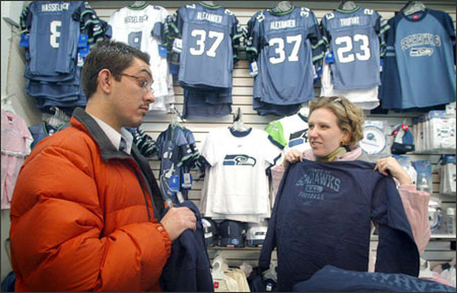 Zaki Abdelhamid and his fiancee, Devin Kearns, hunt for the perfect Seahawks shirt yesterday. Businesses around Qwest Field are excited about the possible windfall from the team's playoff game Saturday against the Rams. Photo: Joshua Trujillo/Seattle Post-Intelligencer / Seattle Post-Intelligencer