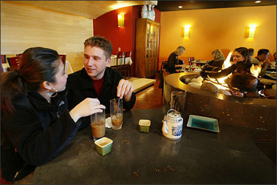 Cindy Pham and Ian McKamey find a quiet spot by the fire pit for their first visit to Tamarind Tree Vietnamese restaurant in the Little Saigon area of Seattle's International District. Photo: / Seattle Post-Intelligencer