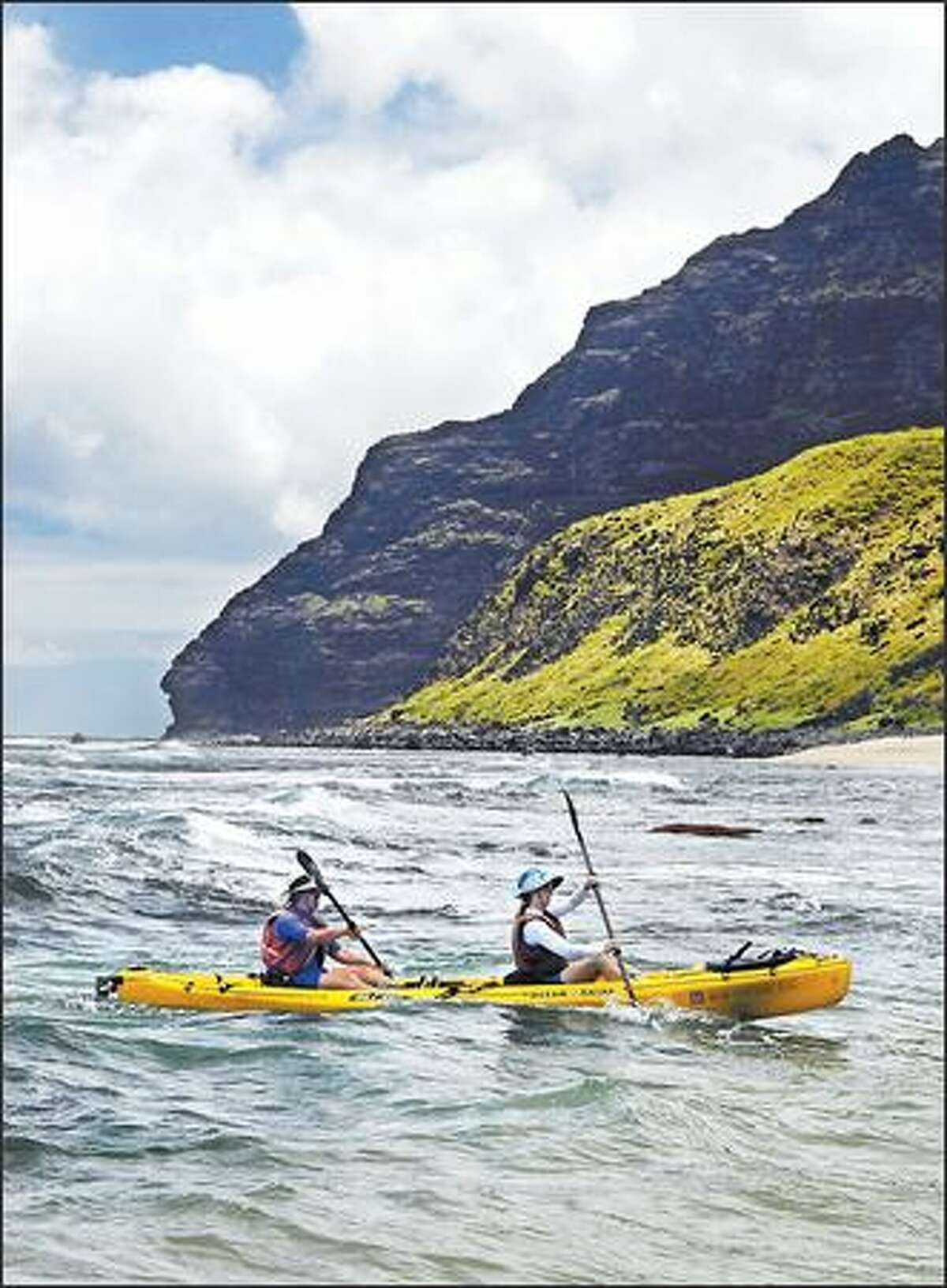 Kayakers head into shore at Polihale State Park after a spectacular 17-mile paddle along the Na Pali Coast.