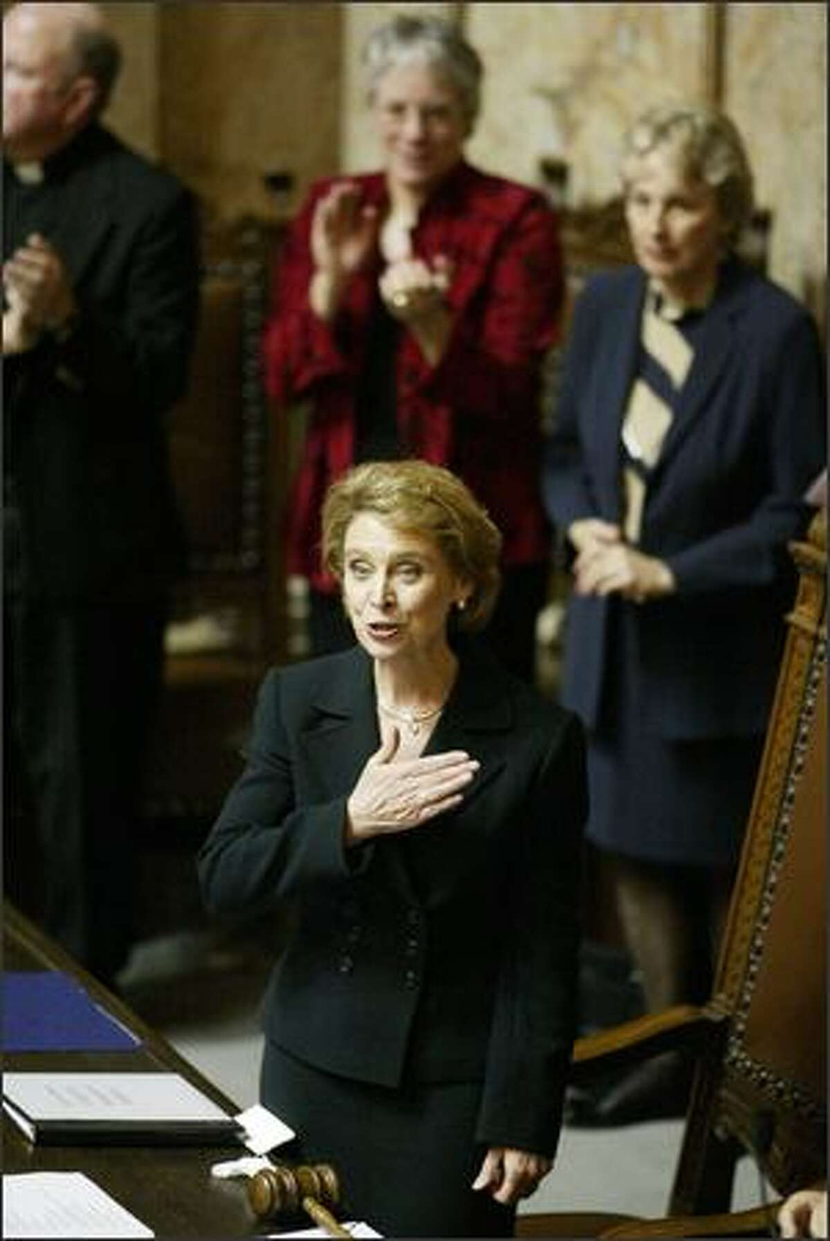With a hand placed over her heart, Christine Gregoire acknowledges her family sitting in the gallery after she was sworn in as governor in the Legislature in Olympia yesterday. - See more photos