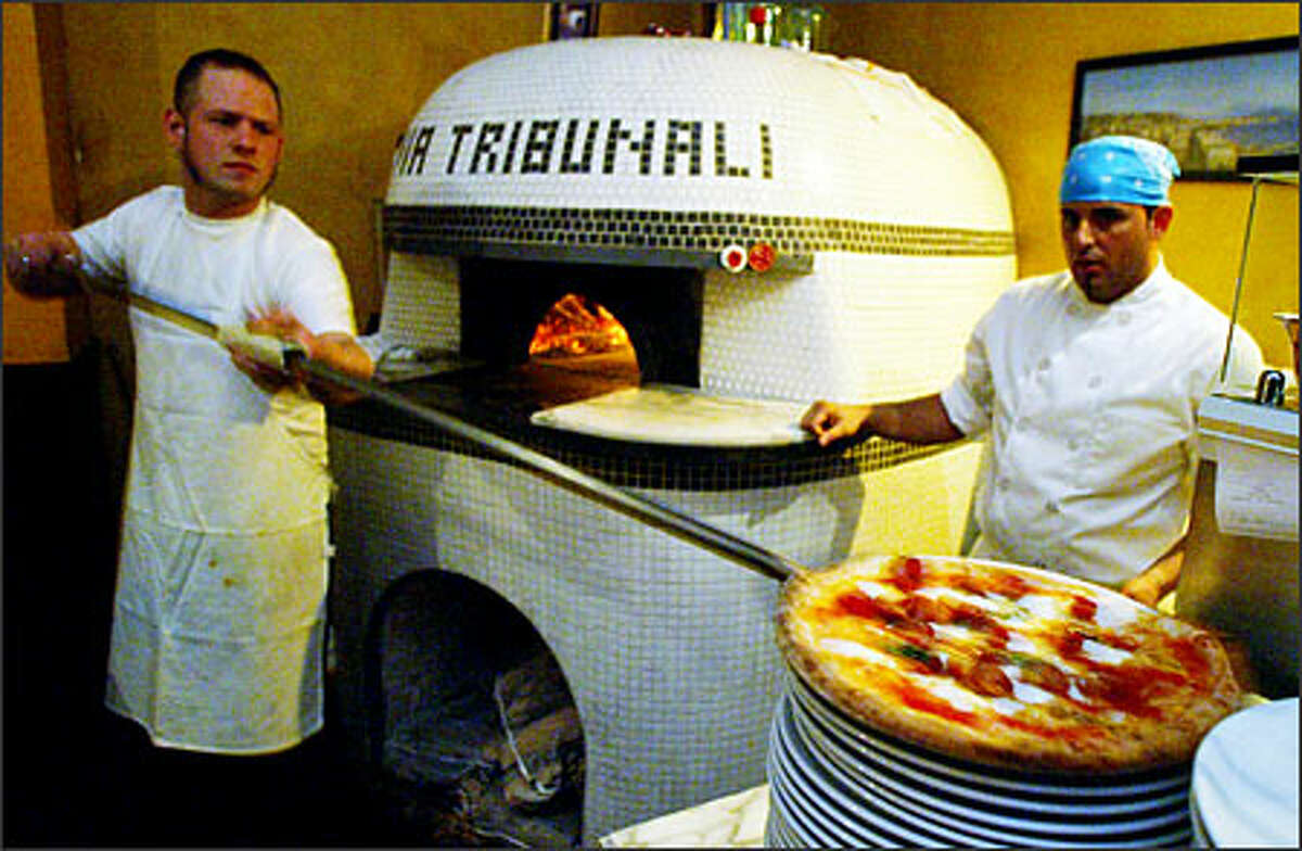 """Pizzaiolo """"Dino"""" (Espedito Santonicola, right) looks on as apprentice pizzaiolo Kevin Wittman, left, removes a pizza from the wood-burning dome at the Via Tribunali on Capitol Hill."""